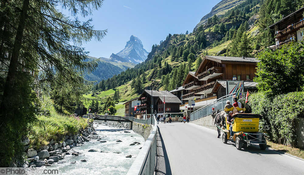 The Matterhorn rises above a horse-drawn carriage along the Matter Vispa (a river tributary of the Rhone). Zermatt, Pennine Alps, Switzerland, Europe.