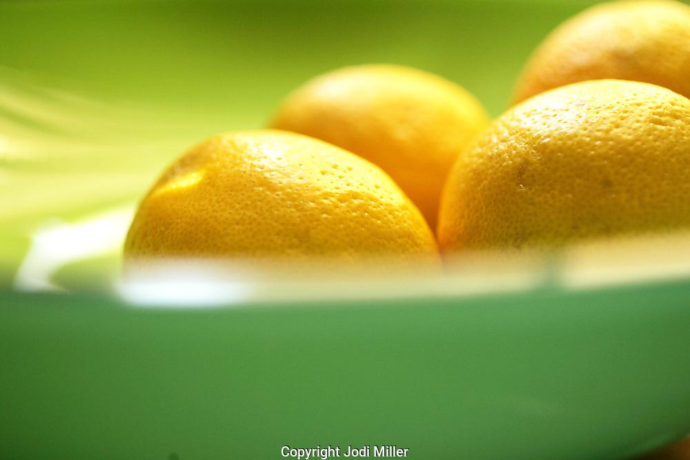 Lemons in a green bowl.