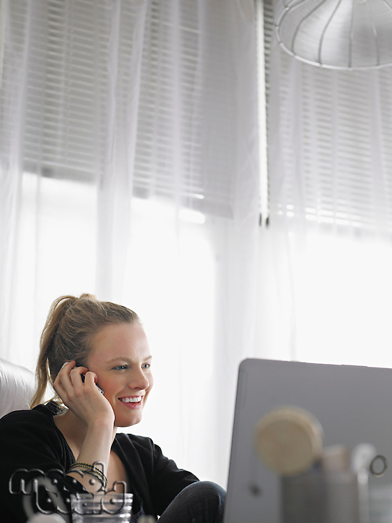 Woman using laptop and mobile phone sitting at desk low angle view