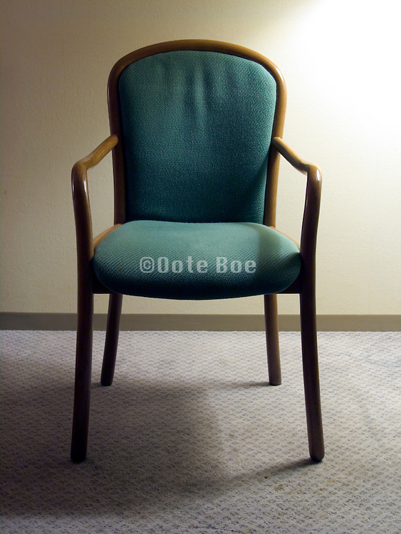 frontal view of an empty chair in a motel room