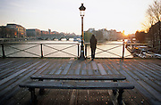A lone, hooded figure stands looking vulnerable while hunched over railings towards the Seine on the Pont des Arts, Paris
