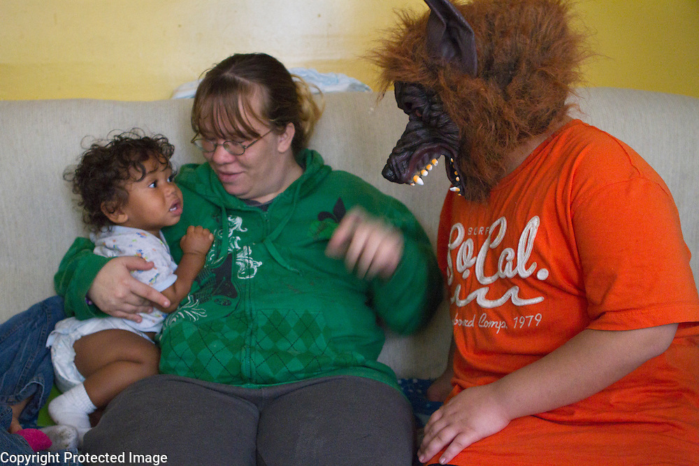 Brenden Chase is comforted by his natural mother while his cousin and foster brother tests his Halloween costume.
