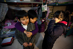 Member of 'Longzaitian' or 'Dragon in the Sky' Shadow Puppet TroupeWang Wenbin (L), 24, is hugged by fellow member Sun Li (C), 22, during a moment of camaraderie while Jia Pan, 22,  looks on in their dormitory  in Beijing, China 29 January 2013. 'Longzaitian' or 'Dragon in the Sky' Shadow Puppet Troupe consists of close to 50 members who look like children but are actually dwarfs with an average age of 22 and height of 1.26 metres. Formed in 2008, the troupe started out with less than ten members but gradually grew in fame and stature, drawing many other dwarfs from all parts of China who seek to be accepted in a community of their own. The troupe provides training, food, accommodation and income for the members as well as a sense of belonging and pride in their work preserving the ancient art of shadow puppetry. Dwarfs have traditionally been viewed as disabled people in China and are often discriminated by mainstream society.