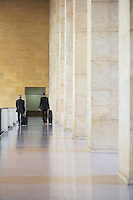 Two business men pulling luggage in airport lobby back view