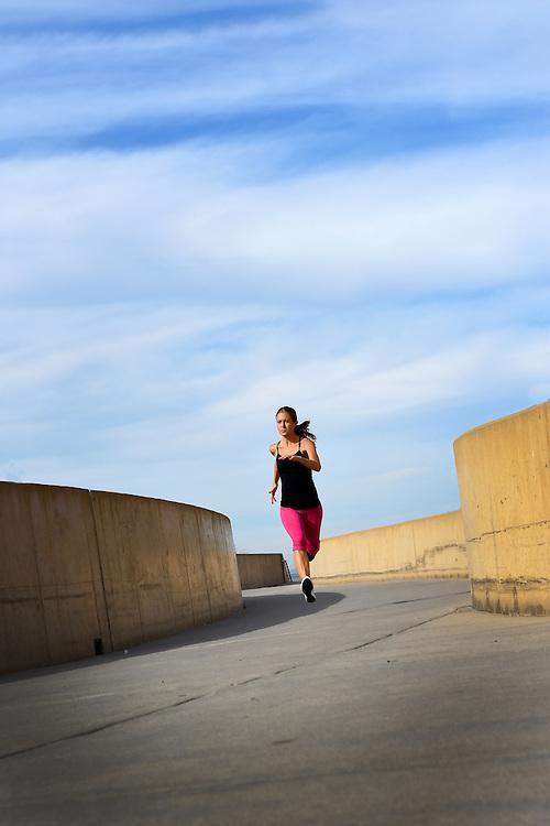 Woman running on bike path at Carlsbad State Beach in Carlsbad, CA.