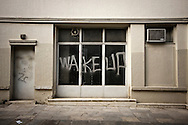 "Greece, Athens, June 2013 - A graffiti on the windows of a closed store in Athens reads ""wake up""."