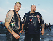 Two male bikers wearing cuts standing together in a wet field at a music festival.