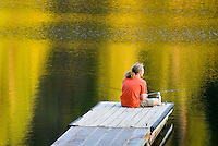 Fisherman in red shirt trying his luck from a dock on Black Pine Lake North Cascades Washington USA