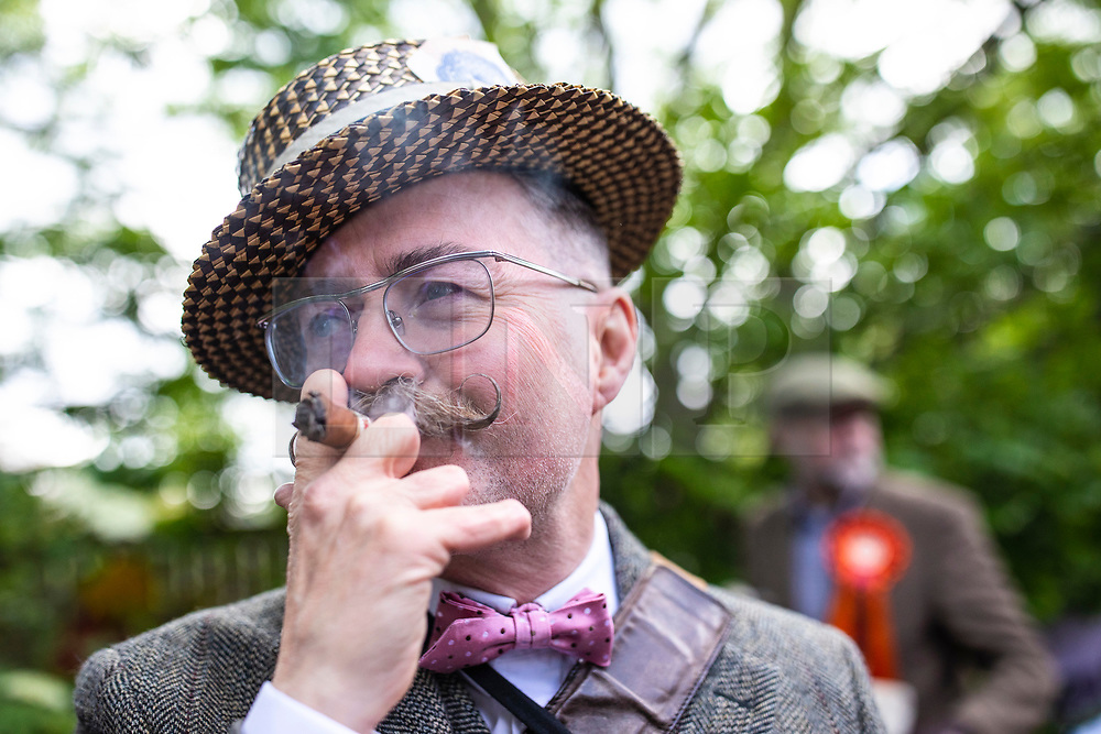 "© Licensed to London News Pictures. 04/05/2019. London, UK. Barry ""Fingers""Copson, a member of the Handlebar Club, smokes a cigar at the start of the annual Tweed Run bicycle ride, in which participants cycle around the capital wearing vintage tweed outfits. Photo credit: Rob Pinney/LNP"
