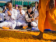 "02 JANUARY 2015 - KHLONG LUANG, PATHUM THANI, THAILAND: People pray as monks walk past them at Wat Phra Dhammakaya on the first day of the 4th annual Dhammachai Dhutanaga (a dhutanga is a ""wandering"" and translated as pilgrimage). More than 1,100 monks are participating in a 450 kilometer (280 miles) long pilgrimage, which is going through six provinces in central Thailand. The purpose of the pilgrimage is to pay homage to the Buddha, preserve Buddhist culture, welcome the new year, and ""develop virtuous Buddhist youth leaders."" Wat Phra Dhammakaya is the largest Buddhist temple in Thailand and the center of the Dhammakaya movement, a Buddhist sect founded in the 1970s.   PHOTO BY JACK KURTZ"
