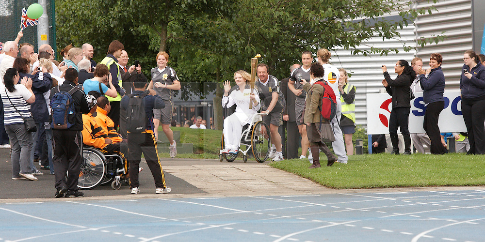 © Licensed to London News Pictures.  09/07/2012. STOKE MANDEVILLE, UK. Gemma Collis, 17, from Aylesbury enters Stoke Mandeville Stadium, birthplace of the Paraolympics,  carrying the Olympic Torch on Day 52 of the Relay through Britain. Gemma was nominated by Sport England for her courage and determination in coping with a condition called Reflex Sympathetic Dystrophy (RSD). She volunteers at a range of events from school festivals to the UK School Games and World Wheelchair Basketball Championships. Photo credit: Cliff Hide/LNP