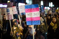 """© Licensed to London News Pictures . 22/02/2018 . Manchester , UK . A protester with a placard reading """" Sisters not cisters """" . 100s of protesters , campaigning against the sexual harassment, abuse, rape and victim-blaming suffered by women, hold a Reclaim the Night march and rally from Owens Park in Fallowfield to the Manchester Academy on Oxford Road . Photo credit : Joel Goodman/LNP"""