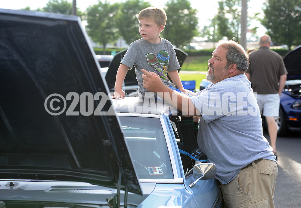 LANGHORNE, PA - JULY 06:  Nicholas Raffaele (L), 5 sits on his father's 1969 Camaro as his dad, Steve Raffaele, 39 of Morrisville, Pennsylvania points out cars during a classic car show at the Blue Fountain Diner that also included music, drawings and other entertainment July 6, 2014 in Langhorne, Pennsylvania. Among the car clubs participating were the Philadelphia Modifiers, Street Rod Clubs, Latin Cruisers and Old Frogs.  (Photo by William Thomas Cain/Cain Images)