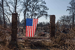 An American flag hang in the rubble of a home in the Coffey Park neighborhood of Santa Rosa, California.