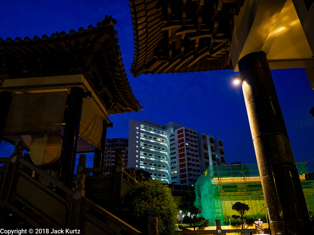 11 DECEMBER 2018 - SINGAPORE:  A Singapore government housing estate is framed by the roof of Foo Hai Ch'an Monastery in the Geylang neighborhood of Singapore. The Geylang area of Singapore, between the Central Business District and Changi Airport, was originally coconut plantations and Malay villages. During Singapore's boom the coconut plantations and other farms were pushed out and now the area is a working class community of Malay, Indian and Chinese people. In the 2000s, developers started gentrifying Geylang and new housing estate developments were built.     PHOTO BY JACK KURTZ