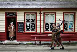 © Licensed to London News Pictures. <br /> 16/10/2016. <br /> Goathland, UK.  <br /> <br /> A woman looks on from her shop as re-enactors in British military clothing march past at Goathland station during the final day of the North Yorkshire Moors Railway Wartime Weekend event. <br /> The annual event brings together re-enactors and enthusiasts along the length of the NYMR heritage steam railway line to recreate the feel of the war years of the 1940's. <br /> <br /> Photo credit: Ian Forsyth/LNP