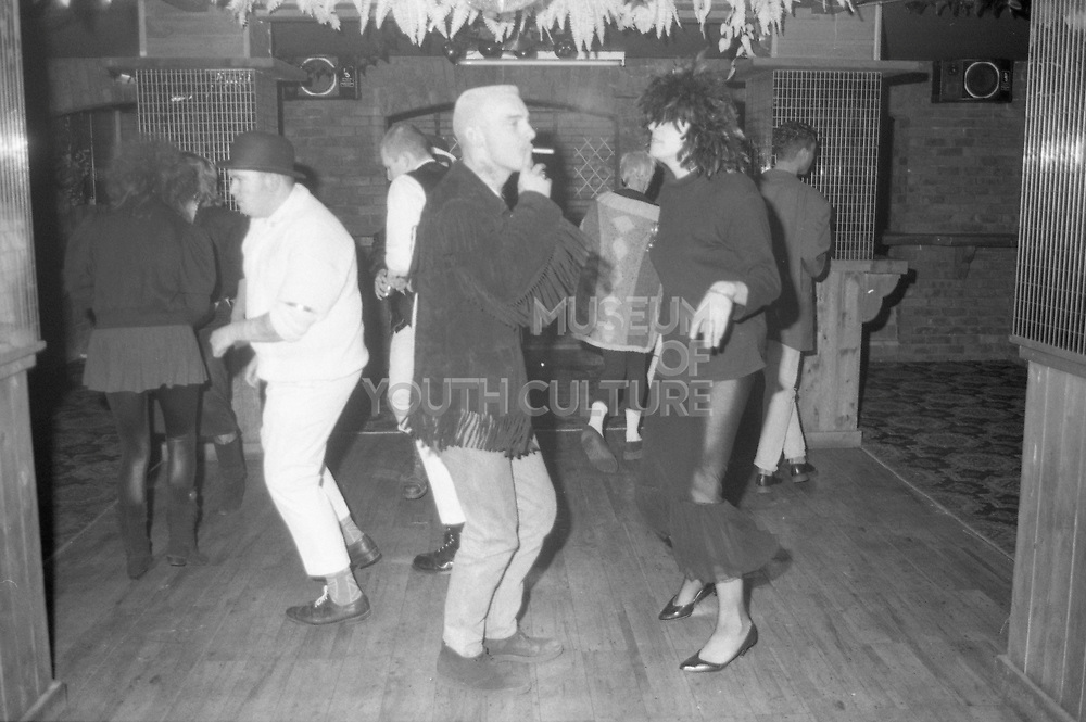 Group of people dancing, including a man in a bowler hat and a man smoking, UK, 1980s.