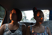 "YANGON, MYANMAR, MARCH 2012: Wai Hnin and Ha Moon on a taxi ride through the streets of central Yangon.<br /> Burma is a country in Transition. And if that hasn't been made clear enough by the political debates and the recent by-elections, meet the Me N Ma Girls, the first girlband in the country.<br /> The timing couldn't be better. After the April 1st elections in 2012 an always increasing number of investors from all over the world has been visiting Myanmar. After decades of military regime and isolation, the strings of censorship have started loosening up. The government censors in fact for years have banned songs and articles, deleting anything that was seen as ""to provocative"" such as leather outfits and colored wigs.<br /> Describing themselves as Myanmar's first all-girl group, under the management of the Australian dancer and choreographer Nicole May, these five women - coming from either Buddhist or Catholic background and formerly known as Tiger Girls - not only have been challenging censorship laws but they're as well trying to win hearts in a society that in many ways remains man-dominated and socially conservative.<br /> In a country that has been locked up for years, the Me N Ma Girls, embracing western pop culture with skimpy outfits and catchy songs, show with every performance the will of the Burmese youth to come out of a decades-long isolation.<br /> Five girls leading a new form of rebellion: the kind that questions roles and cultural norms."