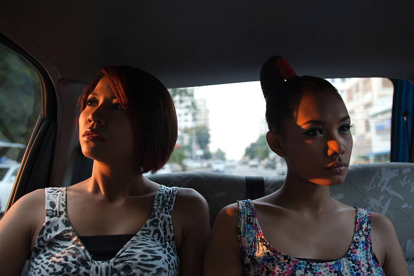 YANGON, MYANMAR, MARCH 2012: Wai Hnin and Ha Moon on a taxi ride through the streets of central Yangon.<br /> Burma is a country in Transition. And if that hasn't been made clear enough by the political debates and the recent by-elections, meet the Me N Ma Girls, the first girlband in the country.<br /> The timing couldn't be better. After the April 1st elections in 2012 an always increasing number of investors from all over the world has been visiting Myanmar. After decades of military regime and isolation, the strings of censorship have started loosening up. The government censors in fact for years have banned songs and articles, deleting anything that was seen as &quot;to provocative&quot; such as leather outfits and colored wigs.<br /> Describing themselves as Myanmar's first all-girl group, under the management of the Australian dancer and choreographer Nicole May, these five women - coming from either Buddhist or Catholic background and formerly known as Tiger Girls - not only have been challenging censorship laws but they're as well trying to win hearts in a society that in many ways remains man-dominated and socially conservative.<br /> In a country that has been locked up for years, the Me N Ma Girls, embracing western pop culture with skimpy outfits and catchy songs, show with every performance the will of the Burmese youth to come out of a decades-long isolation.<br /> Five girls leading a new form of rebellion: the kind that questions roles and cultural norms.