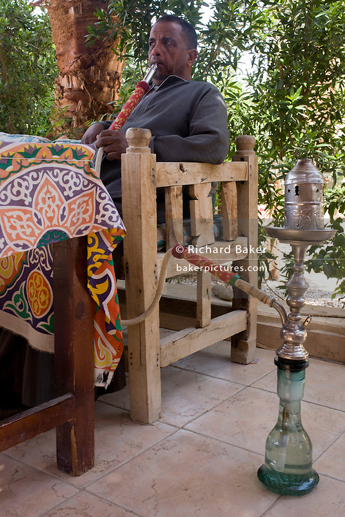 A local man enjoys a shisha in the village of Medinet Habu on the West Bank of Luxor, Nile Valley, Egypt.