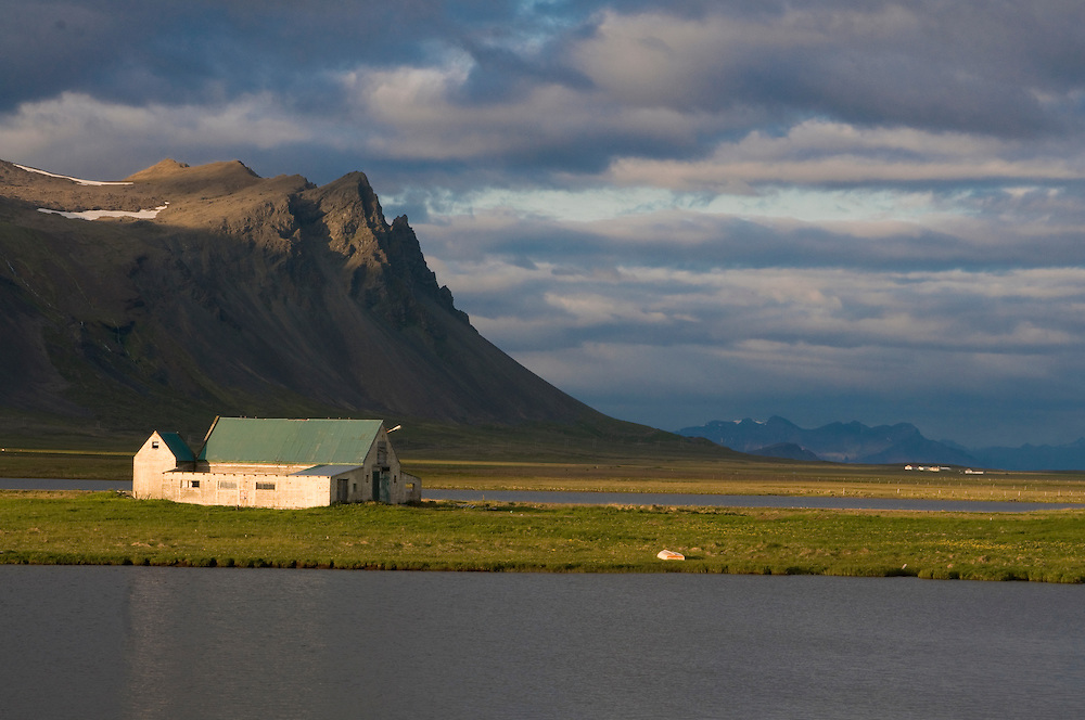 Mountainlandscape with body of water and house. Snaefellsjökull. Iceland.