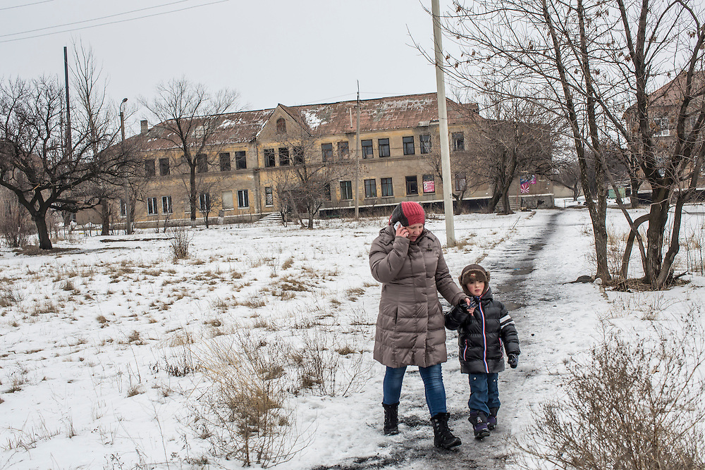 KOMUNAR, UKRAINE - JANUARY 27, 2015: A woman walks with her son in Komunar, Ukraine. The village was the scene of heavy fighting over the summer between pro-Russia rebels and Ukrainian forces, and many residents still face trouble affording food. CREDIT: Brendan Hoffman for The New York Times
