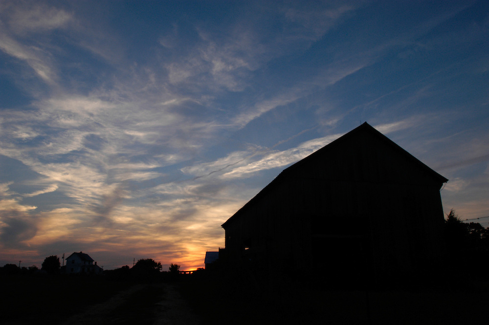 Sunset sky behind a barn