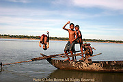 Three young Asian boys are using an old wooden fishing boat as a diving platform on the Mekong River in Kratie, Cambodia. Kratie is the home of the world famous but nearly extinct Irrawaddy dolphin, the only surviving fresh water dolphin in the world that inhabits the Mekong river 10 miles north of this point.