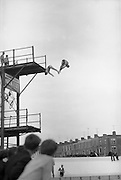 Gallagher High Diving Gala.<br /> 1966.<br /> 01.07.1966.<br /> 07.01.1966.<br /> 1st July 1966.<br /> The Gallagher Sponsored High Diving Gala was held today at The Blackrock Swimming Bath. Sandycove Swimming Club were the holders of the event. <br /> Picture shows a double high dive being performed by Mr Bill Morrison, Former Irish Champion and Mr Eddie Heron of the Sandycove Swimming Club