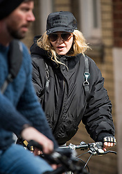 ©  London News Pictures. 10/04/2016. London, UK.  Singer MADONNA leaving her home in central London on her bike, accompanied by security. Madonna was reunited with her son Rocco following a recent court battle over his custody with Madonna's former husband Guy Ritchie. Photo credit: Ben Cawthra/LNP