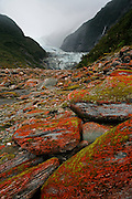 striking orange rock with the blue ice of franz josef glacier rolling down the glacier valley, franz josef, west coast, new zealand