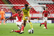 AFC Wimbledon defender Toby Sibbick (20) dribbling and getting shorts pulled during the EFL Trophy match between Charlton Athletic and AFC Wimbledon at The Valley, London, England on 4 September 2018.
