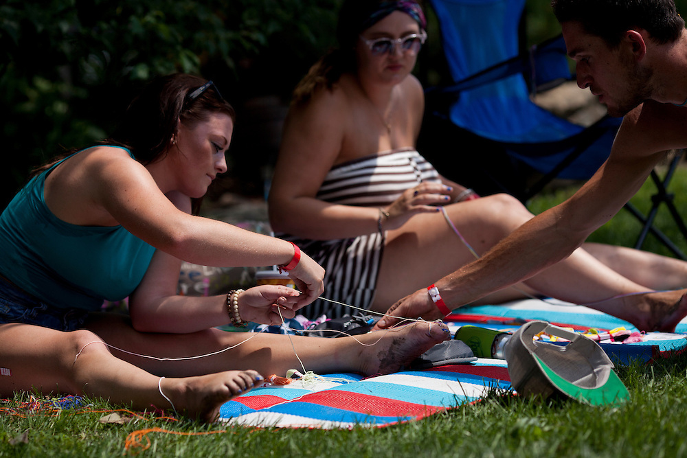 Lauren DeHaven and Emily Carter braid friendship bracelets at Camp Euforia north of Lone Tree on Friday, July 18, 2015. The music festival gathers over a thousand campers and visitors to Jerry Hotz's 120-acre farm every year.