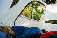 A woman sleeping in a tent in a forest on Lopez Island, Washington, USA.
