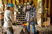 Bob Denman hammers a piece of hot metal to make a Magna Grecia garden tool while his assitant, goose, holds it still.