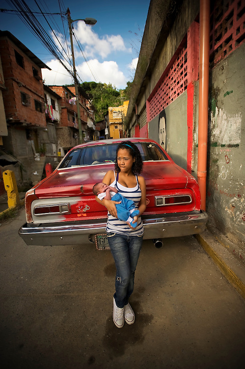 15-year-old Yanaifre Acevedo, holds her newborn baby, Dilan, in a slum in Caracas, Venezuela. Acevedo, who wants to be a professional dancer, said she got pregnant by accident, but that she has a secret plan to have her aunt watch her baby so that she can go back to school. She also plans to get a job so that she and her boyfriend can move into their own apartment together. She says her boyfriend is excited to be a father, but he has hardly visited her and their son.