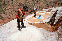 Young boy and his mother working at the salt pans near Maras, Peru.  The pans are fed by a natural spring and the salt has been collected since pre-Inca times.