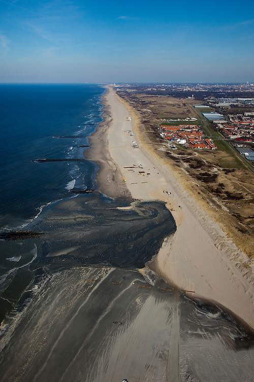 Nederland, Zuid-Holland, Monster, 18-03-2009; Versterking van de kust van Delfland tussen Ter Heijde en 's-Gravenzande door middel van zandsuppletie. Het strand onder in beeld is breder, hier is al gesuppleerd. Meer naar boven, naar het Noordoosten richting Den Haag, moet er nog zand opgespoten worden. Rond de donkere plek is suppletie in volle gang. De kust bij Ter Heijde, het dorpje direkt achter de duinen en met rode daken, is bekend als een van de 'zwakke schakels'. Dit vanwege de geringe breedte van de duinen. De strekdammen in zee zijn de Delflandse Hoofden. .The coast of Delfland, between Hoek van Holland and The Hague, is being strengthened by means of sand-supplementation. The beach in the lower part of the picture is wider, sand has already been supplemented. More to the Northeast (top of picture), sand still needs to be sprayed onto the beach. Around the dark area  sand-supplementation is in progress. The coast at Ter Heijde, the red-roofed village behind the dunes, is one of the so-called 'weak-links' because of the weakness of the dunes..Swart collectie, luchtfoto (toeslag); Swart Collection, aerial photo (additional fee required); .foto Siebe Swart / photo Siebe Swart