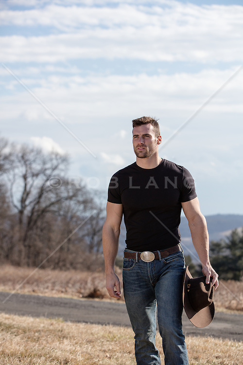 cowboy holding his hat on a ranch