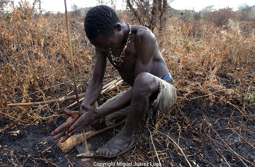 Yaeda Valley, Tanzania: Hoya, a Hadzabe hunter gatherer, makes fire the old fashioned way: with sticks. The Hadzabe are the second oldest people on earth, with a culture dating back at least 60,000 years, or shortly after human evolution. There are fewer than 1,500 left, all in this northern corner of Tanzania, where they are on the verge of losing their tribal hunting ground to a safari company. (PHOTO:  MIGUEL JUAREZ LUGO)