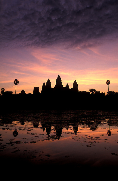 CAMBODIA - Angkor Wat.The imposing towers rise above the baray at dawn