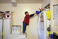 Jeremiah Hall, 4, climbs on a freezer to get candy when his mother Betty Aquino is not looking in the family's  Bridgeport, Connecticut home March 17, 2015. Hall has been suspended from school numerous times in the past few months. Suspensions in Connecticut&rsquo;s K-12 schools have dropped 7% in the last two years, but one category of students saw a 22% increase over that same time period: Children seven and under. Critics say suspending children at this age doesn&rsquo;t correct the behavior of young kids who may not fully understand the consequences of their actions. Advocates are trying to pass a law that would prohibit suspending children under the age of 7. <br /> CREDIT: Michelle McLoughlin for The Wall Street Journal