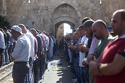 July 19, 2017 - Jerusalem, Israel - 19.07.17 Lion's Gate, Jerusalem- Muslim's hold afternoon prayer outside Lion's Gate as Israeli Police look on. Clashes between Muslim protesters and police outside Lion's Gate in Jerusalem's Old City. (Credit Image: © Louise Wateridge/Pacific Press via ZUMA Wire)