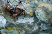 Varied rock colours in a the fast flowing river of the Afon Glasyn in the Nant Glaslyn Pass near Beddgelert, Snowdonia. This river flows directly from the lake below Snowdon's summit.
