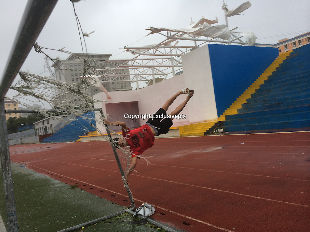 ZHANJIANG, CHINA - SEPTEMBER 16: (CHINA OUT) <br /> <br /> Student Poses In Typhoon Kalmaegi<br /> <br /> A university student poses with a goal for fun when typhoon Kalmaegi passing Zhanjiang on September 16, 2014 in Zhanjiang, Guangdong province of China. Typhoon Kalmaegi hit China\'s South coastal city Zhanjiang on September 16. <br /> ©Exclusivepix