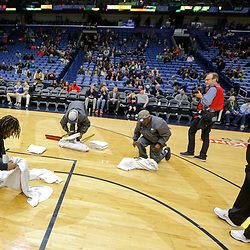 Feb 7, 2018; New Orleans, LA, USA; New Orleans Pelicans equipment manager David Jonanovic (right) inspects the court during a delay due to moisture on the court from a roof leak before the start of a game between the New Orleans Pelicans and the Indiana Pacers at the Smoothie King Center. Mandatory Credit: Derick E. Hingle-USA TODAY Sports