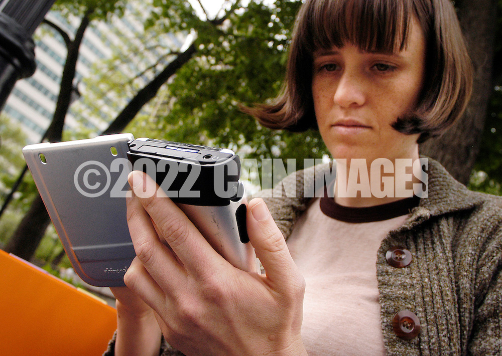 PHILADELPHIA - MAY 2:  Emily Cook uses a PDA wireless device to connect to the internet at Love Park, part of the Wireless Philadelphia project May 2, 2005 in Philadelphia, Pennsylvania. Philadelphia's wireless internet plam is to have low-cost wifi internet access available throughout the city. (Photo by William Thomas Cain)
