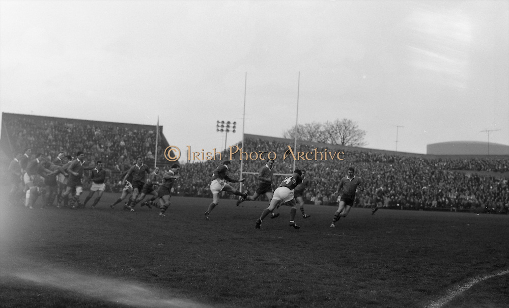Bresnihan, left, kicks ahead over two Australians to Duggan, number 14, running around Australians,..Irish Rugby Football Union, Ireland v Australia, Tour Match, Landsdowne Road, Dublin, Ireland, Saturday 21st January, 1967,.21.1.1967, 1.21.1967,..Referee- M Joseph, Welsh Rugby Union, ..Score- Ireland 15 - 8 Australia, ..Irish Team, ..T J Kiernan,  Wearing number 15 Irish jersey, Full Back, Cork Constitution Rugby Football Club, Cork, Ireland,..A T A Duggan, Wearing number 14 Irish jersey, Right Wing, Landsdowne Rugby Football Club, Dublin, Ireland,..F P K Bresnihan, Wearing number 13 Irish jersey, Right Centre, University College Dublin Rugby Football Club, Dublin, Ireland, ..H H Rea, Wearing number 12 Irish jersey, Left Centre, Edinburgh University Rugby Football Club, Edinburgh, Scotland, ..P J McGrath,  Wearing number 11 Irish jersey, Left Wing, University college Cork Rugby Football Club, Cork, Ireland,  ..C M H Gibson, Wearing number 10 Irish jersey, Stand Off, N.I.F.C, Rugby Football Club, Belfast, Northern Ireland, ..B F Sherry, Wearing number 9 Irish jersey, Scrum Half, Terenure Rugby Football Club, Dublin, Ireland, ..K G Goodall, Wearing number 8 Irish jersey, Forward, Newcastle University Rugby Football Club, Newcastle, England, ..M G Doyle, Wearing number 7 Irish jersey, Forward, Edinburgh Wanderers Rugby Football Club, Edinburgh, Scotland, ..N Murphy, Wearing number 6 Irish jersey, Forward, Cork Constitution Rugby Football Club, Cork, Ireland,..M Molloy, Wearing number 5 Irish jersey, Forward, University College Galway Rugby Football Club, Galway, Ireland,  ..W J McBride, Wearing number 4 Irish jersey, Forward, Ballymena Rugby Football Club, Antrim, Northern Ireland,..P O'Callaghan, Wearing number 3 Irish jersey, Forward, Dolphin Rugby Football Club, Cork, Ireland, ..K W Kennedy, Wearing number 2 Irish jersey, Forward, C I Y M S Rugby Football Club, Belfast, Northern Ireland, ..T A Moroney, Wearing number 1 Irish jersey, Forward, University College Dubl