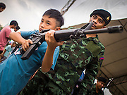 10 JANUARY 2015 - BANGKOK, THAILAND: A Thai child handles a M-16 assault rifle during Children's Day celebrations at a Royal Thai Army base in Bangkok. National Children's Day falls on the second Saturday of the year. Thai government agencies sponsor child friendly events and the military usually opens army bases to children, who come to play on tanks and artillery pieces. This year Thai Prime Minister General Prayuth Chan-ocha, hosted several events at Government House, the Prime Minister's office.    PHOTO BY JACK KURTZ