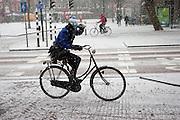 Een meisje fietst door de sneeuw met haar hand boven haar ogen om de sneeuw tegen te houden
